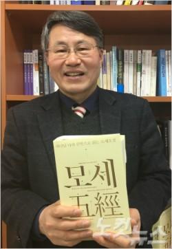 숭실대 김회권 교수가 연구실에서 최근 출간한 '하나님나라 신학으로 읽는 모세오경' 책을 들고 환하게 웃고있다.