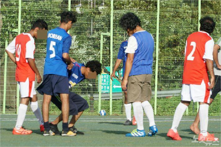 아흐메드(23)가 축구 중에 쓰러지자 예멘청년들이 부축해주고 있다. <사진=고상현 기자>