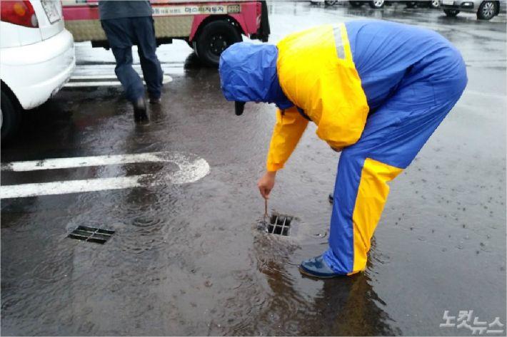 용담2동 주민센터 공무원이 제주시 용담동 한천 인근 공영주차장 배수구를 점검하고 있다. <사진=고상현 기자>