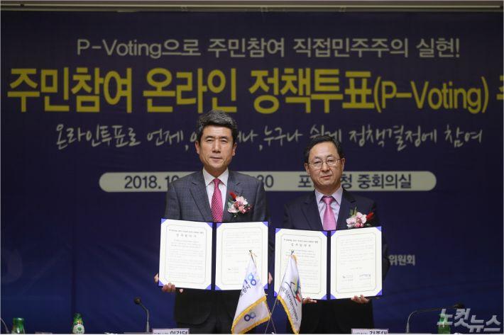 이강덕(왼쪽) 포항시장과 경북선관위 김종대 사무처장이 주민참여 온라인 정책투표 업무협약서를 들고 있다(사진=포항시 제공)