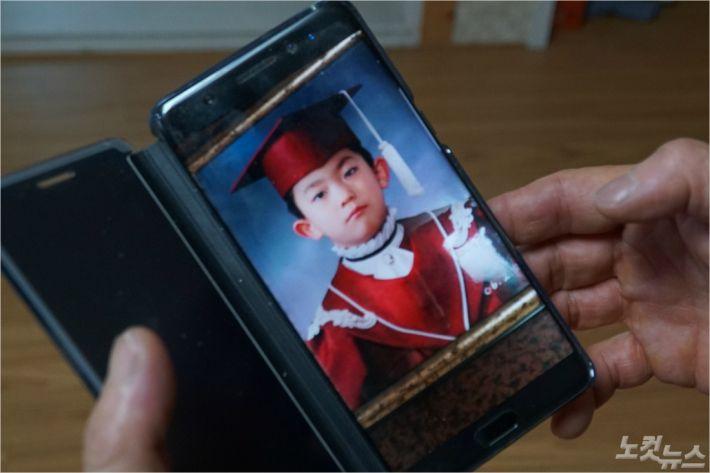 김형보씨가 고 김선웅군의 어린 시절 모습을 보여주고 있다. <사진=고상현 기자>