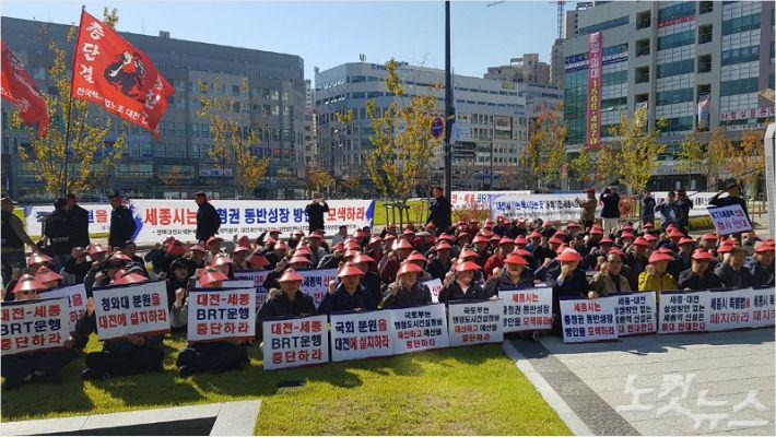 """대전 택시 5개 단체 관계자 100여 명이 12일 세종시청 앞에서 열린 집회에서 """"세종시와 대전시의 택시 사업구역을 통합 운영하라""""고 외치고 있다. (사진=고형석 기자)"""
