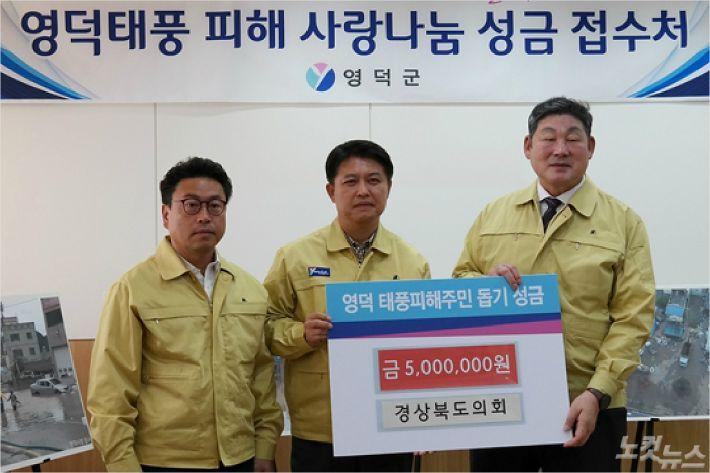 경북도의회 장경식 의장(맨 오른쪽)이 이희진 영덕군수(가운데)에게 성금을 전달하고 있다.(사진=영덕군)