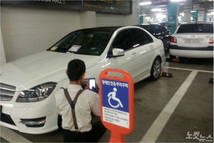 장애인전용주차구역에 불법주차한 차량이 단속되고 있다.(자료사진)