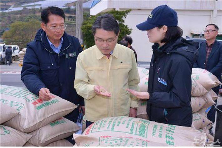 권오봉 여수시장(가운데)이 7일 돌산 도실마을 공공비축미곡 매입현장에서 쌀을 살펴보고 있다(사진=여수시)