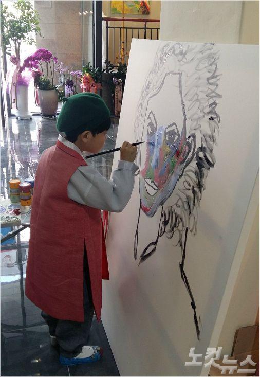 관중 앞에서 그림 작업을 하고 있는 화가 김하민(8)군.<사진=성원아트홀 제공>