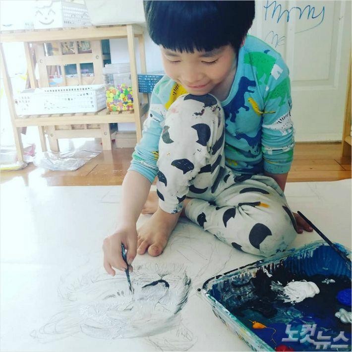 집에서 그림그리기 작업을 하고 있는 화가 김하민(8)군.<사진=성원아트홀 제공>