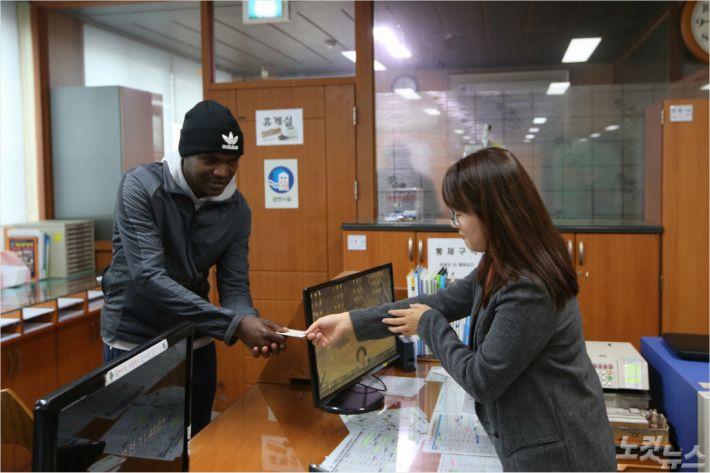 케냐 출신 마라토너 윌슨 로야나에 에루페가 청양군 정산면사무소에서 주민등록증을 받고 있다. (사진=청양군 제공)