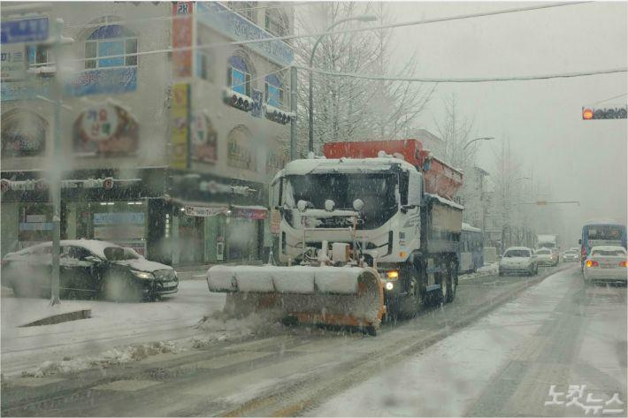 24일 강원 춘천에 첫눈이 내리고 있는 가운데 제설차량들이 도로 제설작업에 나서고 있다.(사진=박정민 기자)