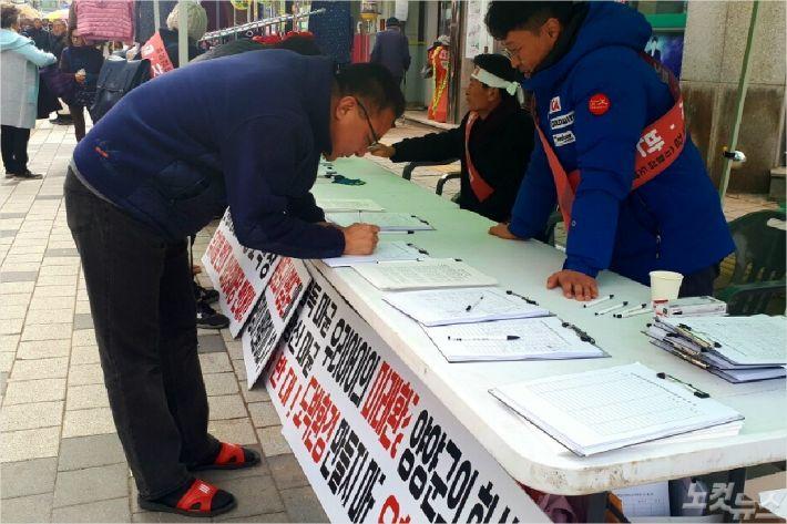 지역민들이 '화상경마장 유치'에 반대서명을 하고 있다. (사진=유선희 기자)