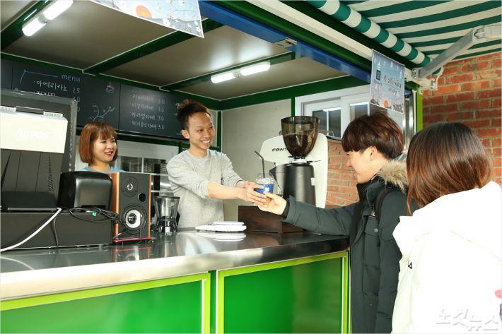 한남대 베트남 유학생들이 창업한 카페에서 손님에게 커피를 건네고 있다. (사진=한남대 제공)