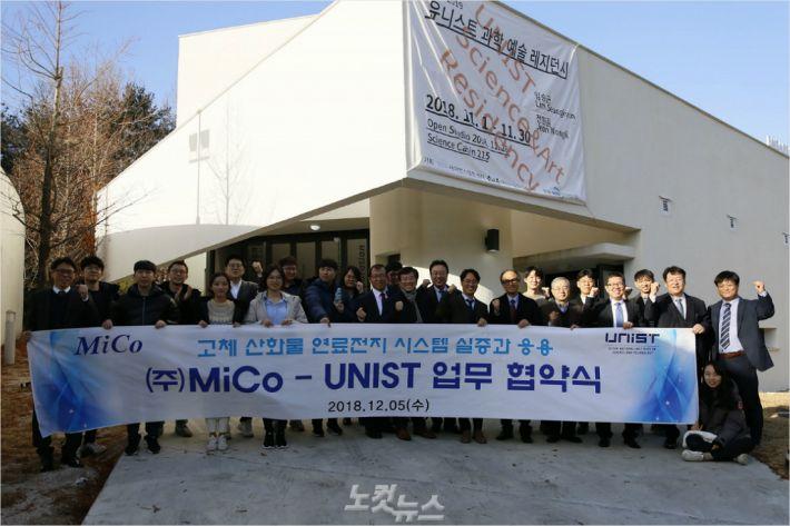 UNIST(울산과학기술원)와 민간기업 (주)미코가 5일 대학 학술정보관에서 고체 산화물 연료전지(SOFC)를 실용화하기 위한 공동 연구 업무협약을 체결했다. 체결식에 참석한 사람들이 과일집 앞에서 단체 사진을 찍고 있다.(사진 = UNIST 제공)
