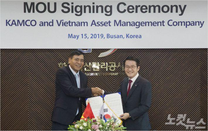 사진 오른쪽부터 문창용 캠코 사장과 응우옌 티엔 동 베트남자산관리공사 회장이 '베트남 부실채권 정리 및 공사 운영 등에 대한 업무 협력 양해각서(MOU)'를 체결하고 있다 (사진 = 캠코 제공)