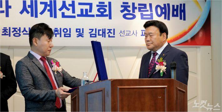 스펠라 세계선교회 대표회장 최정식 목사(오른쪽)와 선교사로 파송받은 김대진 목사(왼쪽)의 파송패 전달식.