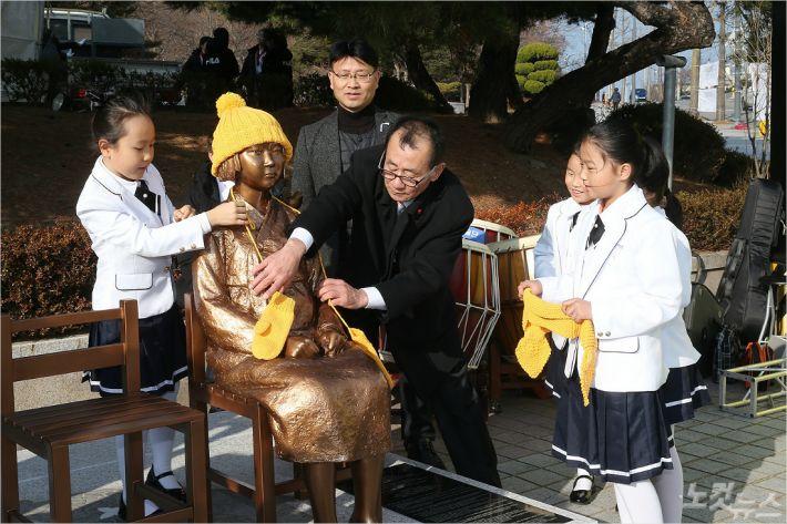 평화의 소녀상 제막식에 참석한 어린이들이 소녀상에 털모자와 목도리, 양말 등을 씌우고 있다. (사진=동해시청 제공)