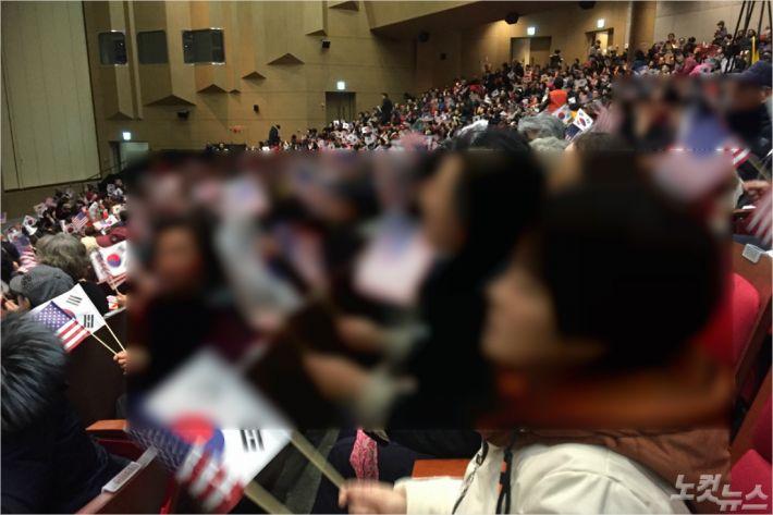 기도회 참석자들. 태극기와 성조기를 흔들며 찬송을 부르고 있다.