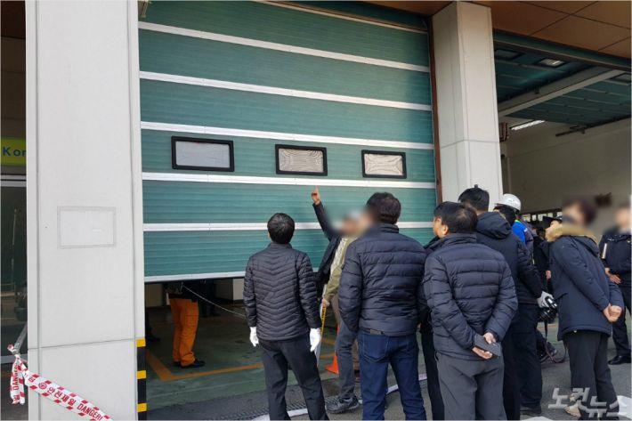지난 2일 부산 사하소방서 다대119안전센터에서 열린 국과수 현장감식에서 관계자들이 추락한 셔터를 살펴보고 있다. (사진=부산CBS 박진홍 기자)