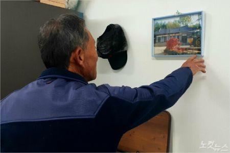 박만호(73) 할아버지가 예전에 살던 집을 찍어둔 사진을 가만히 바라보고 있다. (사진=유선희 기자)