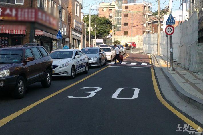 부산 안전속도 5030 시행으로 부산지역 한 이면도로에 시속 30km 제한이라고 적혀 있는 모습.(사진=부산경찰청 제공)
