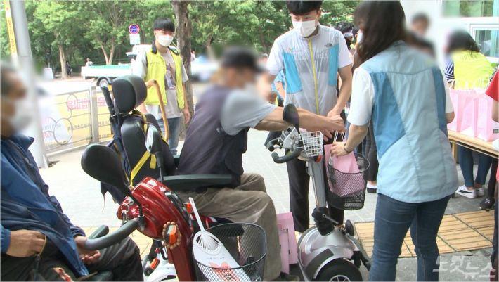 지난 17일, 사상구 장애인 복지관 앞에서 열린 삼계탕 나눔 행사에서 대상자들이 삼계탕을 받고 있다.