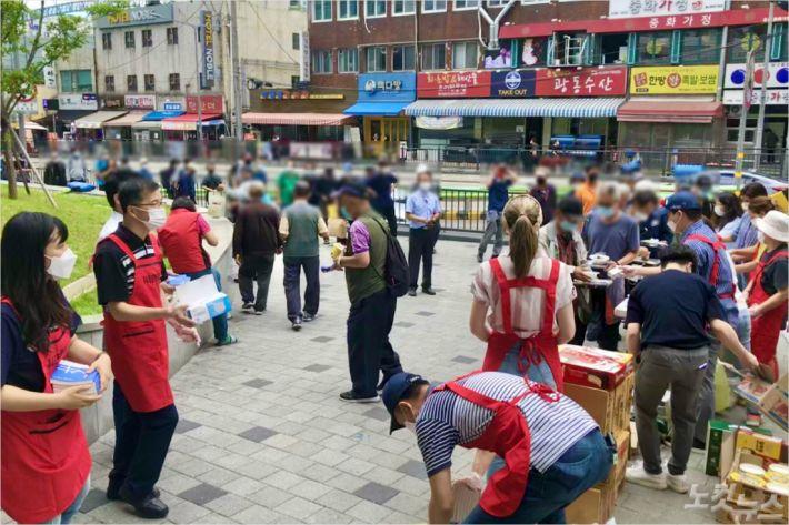 지난달 25일 서울 용산구 용산역 앞에서 노숙인들에게 무료 급식 봉사활동을 펼치는 주님기쁨의교회 영어예배부 교인들.