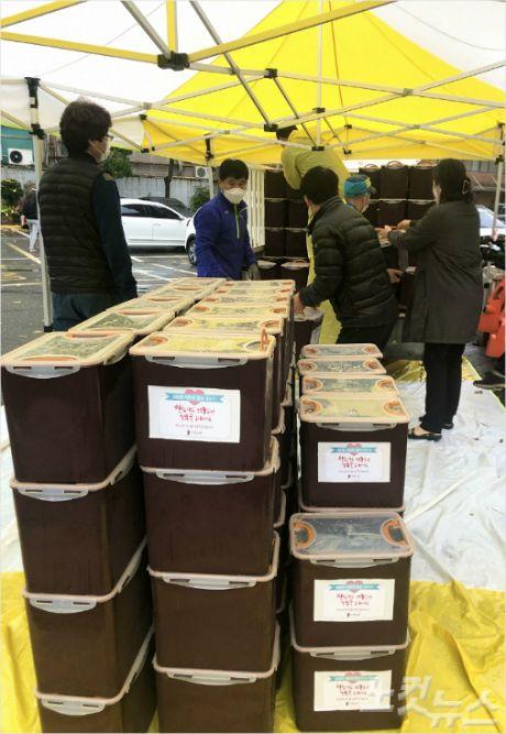 신일교회에서 홀몸 어르신들을 위해 구입한 김치 250통을 주민센터 차량으로 옮기는 모습.