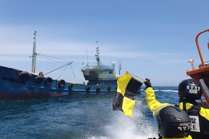 군산해경 해상특수기동대원들이 중국어선에 정선 명령을 내리고 있다. 군산해경 제공