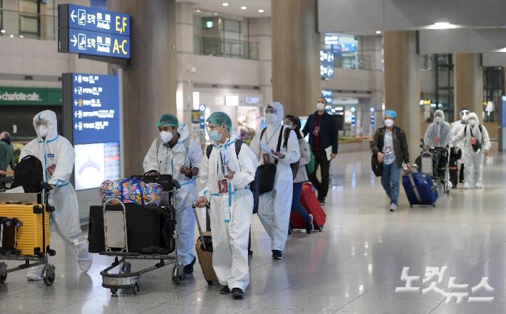 인천국제공항에서 방역복을 입은 외국인들이 입국장을 나서고 있다 이한형 기자
