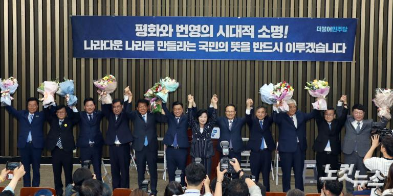 더불어민주당, 당선인들과 꽃다발 들고 환호