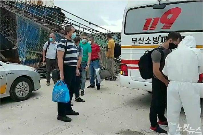 지난달 24일 부산 영도구 한 수리조선소에서 코로나19 확진 판정을 받은 러시아 선박 페트르원호 선원들이 부산의료원으로 이송되고 있다. (사진=부산소방재난본부 제공)