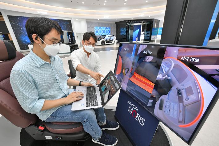 현대모비스가 세계 최초로 개발한 뇌파 측정 기반 운전자 모니터링 시스템, '엠브레인'을 개발한 연구원들이 관련 기술을 시험하는 모습. 현대모비스 제공