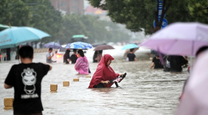지난 20일 중국 중부 허난성 성도인 정저우에 폭우가 쏟아지는 가운데 시민들이 물에 잠긴 거리를 걷고 있다. 연합뉴스