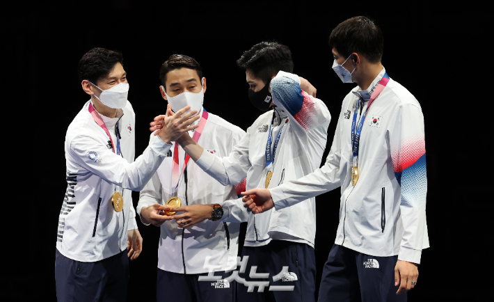 Bon-gil Koo (from left), Jeong-hwan Kim, Jun-ho Kim, and Sang-wook Oh congratulate each other at the awards ceremony for the men's saber team finals in fencing at the Tokyo Olympics held at Makuhari Messe B Hall in Chiba, Japan on the 28th.  Olympic Photography Foundation
